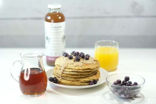 vegan pancakes next to a bottle of maple syrup, orange juice, blueberries and thrive remedies