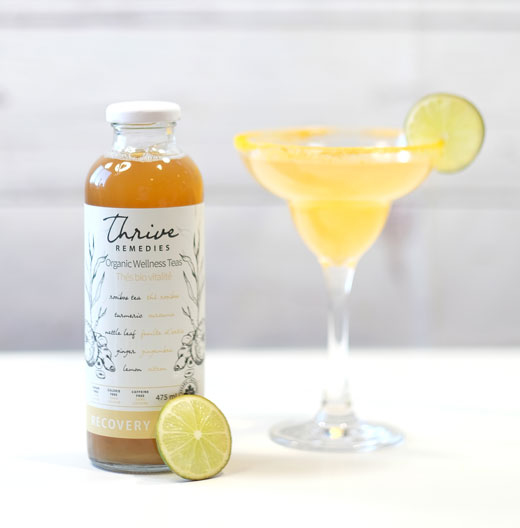 ginger margarita with a bottle of thrive and a lime