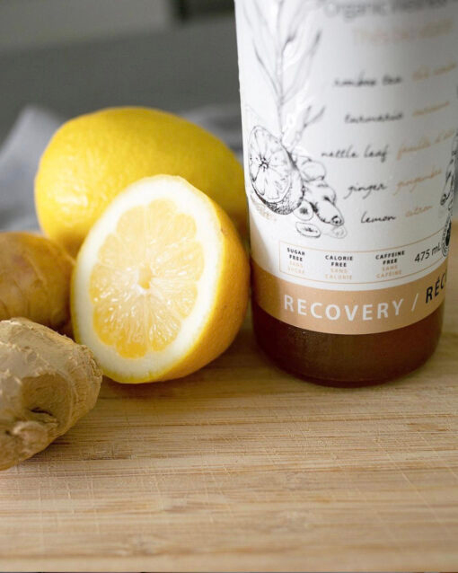 bottle of thrive remedies sitting on a cutting board with lemons and ginger