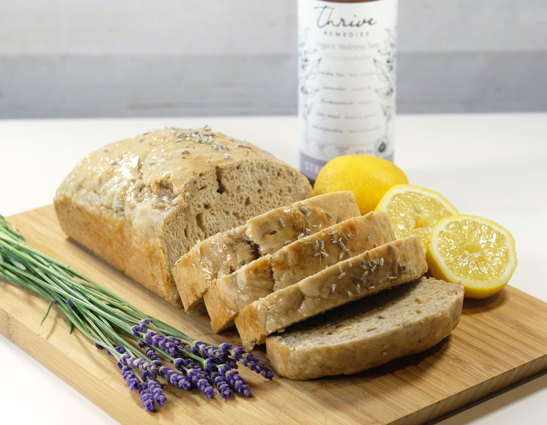 lemon lavender loaf on a cutting board next to some fresh lavender flowers and lemons