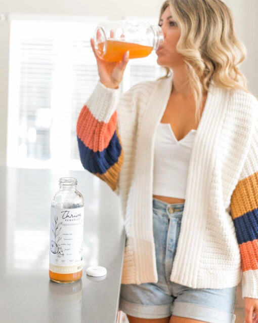 woman drinking thrive remedies recovery flavour out of a mason jar