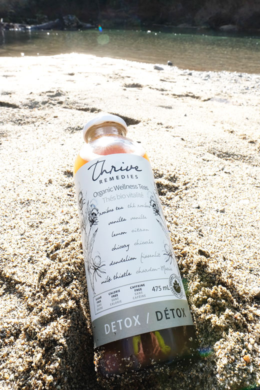 bottle of detox in the sand at a lake