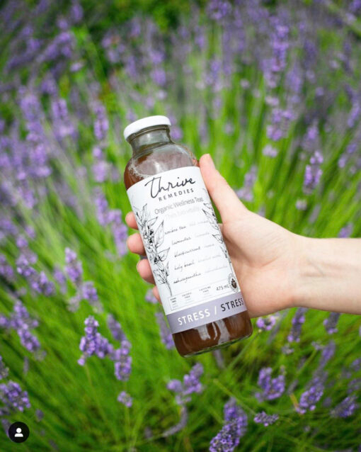 woman's hand holding a bottle of stress over a field of lavender