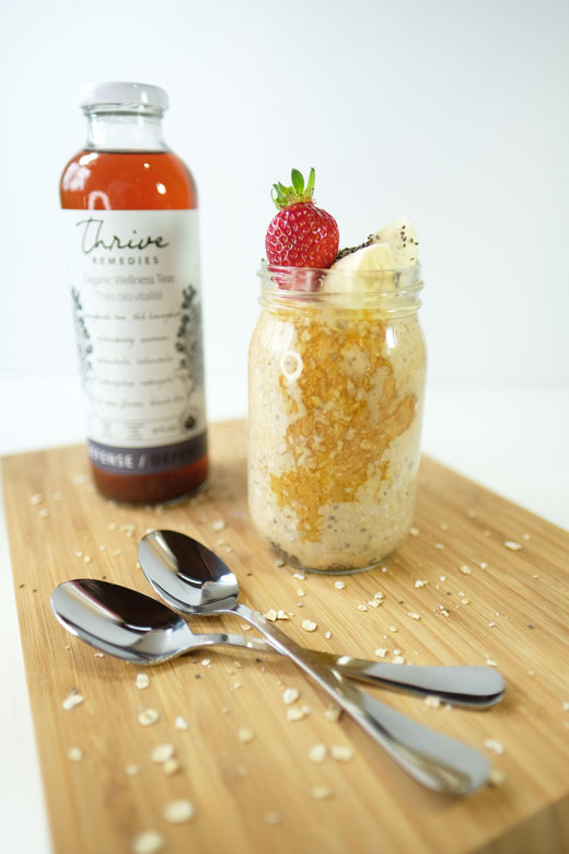 overnight oats on a wooden cutting board next to a bottle of defense