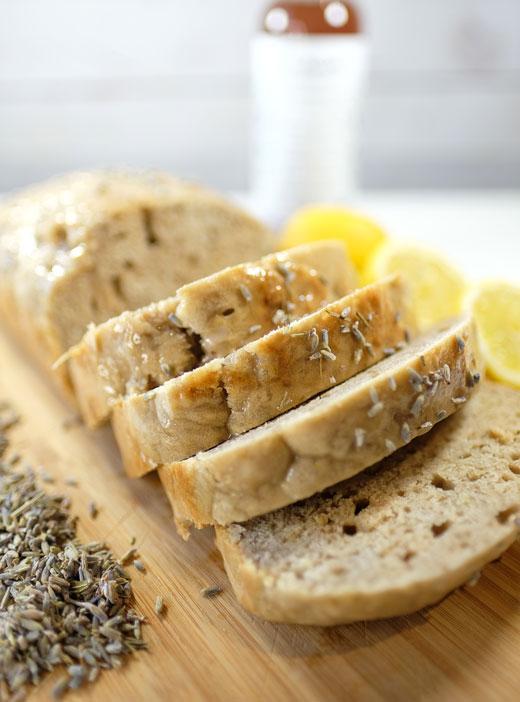 vegan lemon loaf on a cutting board next to some lemons